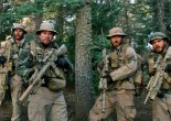 "This photo released by Universal Pictures shows, from left, Taylor Kitsch, as Michael Murphy, Mark Wahlberg as Marcus Luttrell, Ben Foster as Matt ""Axe"" Axelson, and Emile Hirsch as Danny Dietz in a scene from the film, ""Lone Survivor."" In the age of the superhero, the movies' most reliable real-life hero has been the Navy SEAL. ""Lone Survivor,"" is the latest in a string of films, including ""Zero Dark Thirty"" and ""Act of Valor"" to honor the Navy's special operations force with as much faithfulness as the filmmakers could muster. (AP Photo/Universal Pictures)"
